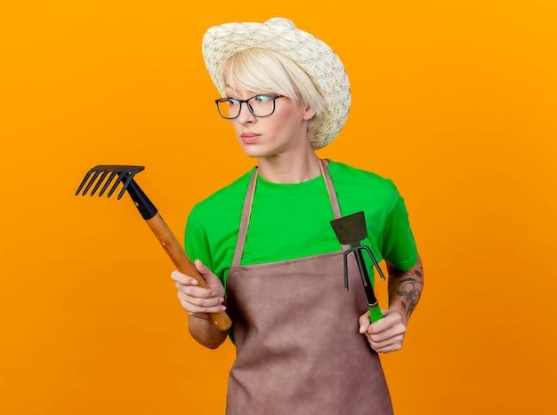 Młoda ogrodniczka kobieta z krótkimi włosami w fartuchu i kapeluszu, trzymająca matę i mini grabie, wyglądająca na zdezorientowaną, próbująca dokonać wyboru stojąc na pomarańczowym tle