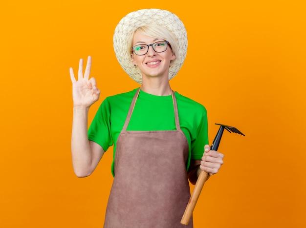 Młoda ogrodniczka kobieta z krótkimi włosami w fartuchu i kapeluszu trzymająca mini grabie patrząc na kamerę uśmiechnięta wesoło pokazująca znak ok stojąc na pomarańczowym tle