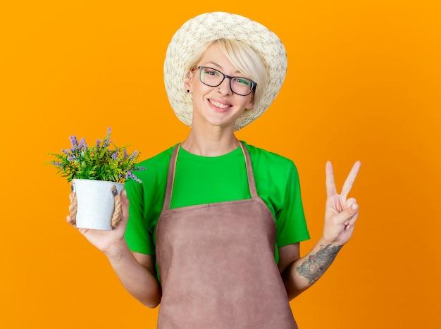 Młoda ogrodniczka kobieta z krótkimi włosami w fartuchu i kapeluszu trzymająca roślinę doniczkową patrząc na kamery uśmiechnięta z radosną twarzą pokazującą znak v stojący na pomarańczowym tle