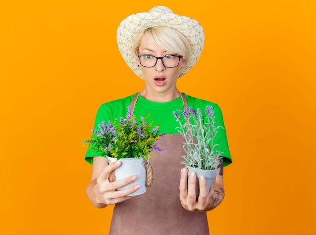 Młoda ogrodniczka kobieta z krótkimi włosami w fartuchu i kapeluszu trzymająca rośliny doniczkowe patrząc na nich zdezorientowana, próbując dokonać wyboru stojąc na pomarańczowym tle