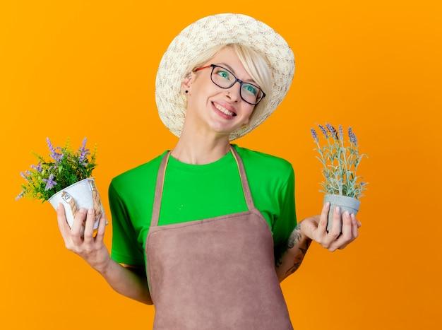 Młoda ogrodniczka kobieta z krótkimi włosami w fartuchu i kapeluszu trzymająca rośliny doniczkowe patrzy na bok uśmiechając się ze szczęśliwą twarzą stojącą na pomarańczowym tle