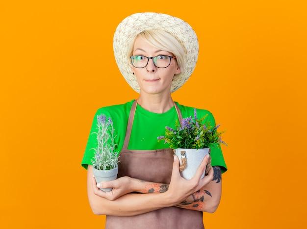 Młoda ogrodniczka kobieta z krótkimi włosami w fartuchu i kapeluszu trzymająca rośliny doniczkowe patrzy na kamerę ze sceptycznym uśmiechem stojąc na pomarańczowym tle