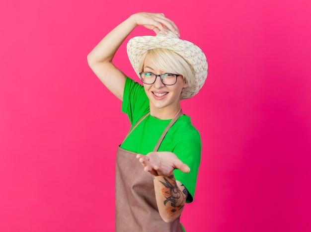 Młoda ogrodniczka kobieta z krótkimi włosami w fartuchu i kapeluszu, uśmiechając się radośnie