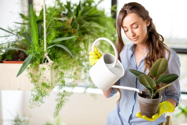 Młoda ogrodniczka opiekująca się roślinami stojąca z konewką na drabinie w oranżerii