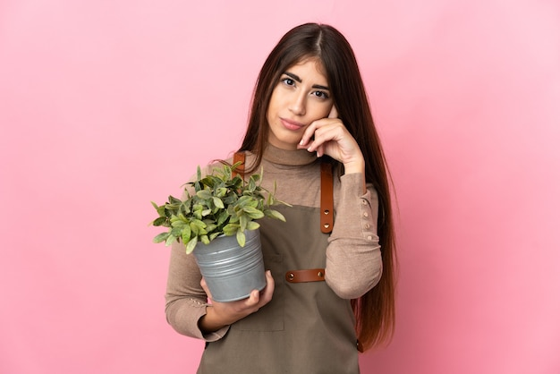 Młoda ogrodniczka trzymająca roślinę odizolowaną na różowym tle myśląca o pomyśle