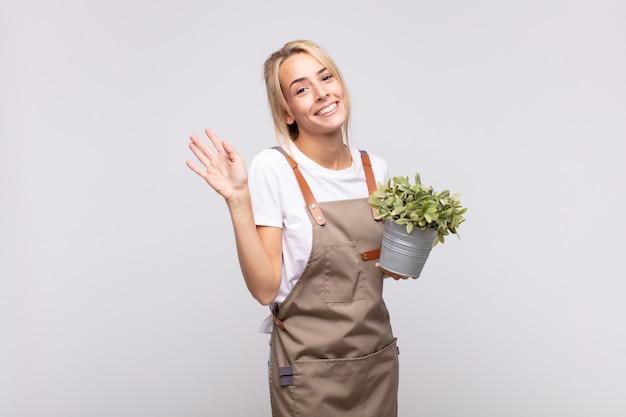 Młoda ogrodniczka uśmiecha się radośnie i wesoło, macha ręką, wita i wita lub żegna się