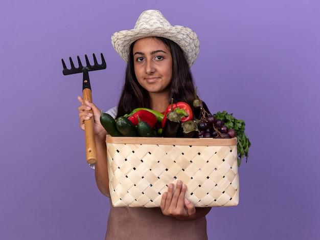 Młoda ogrodniczka w fartuchu i letnim kapeluszu trzyma skrzynię pełną warzyw i mini grabie z uśmiechem na twarzy stojącej nad fioletową ścianą