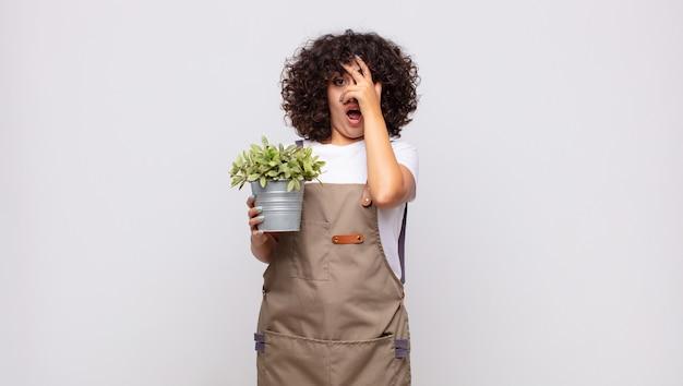 Młoda ogrodniczka wyglądająca na zszokowaną, przestraszoną lub przerażoną, zakrywającą twarz dłonią i zaglądającą między palce