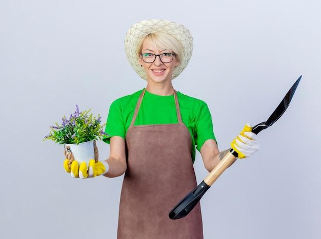 Młoda ogrodniczka z krótkimi włosami w fartuchu i kapeluszu trzymająca łopatę i roślinę doniczkową z uśmiechem na twarzy