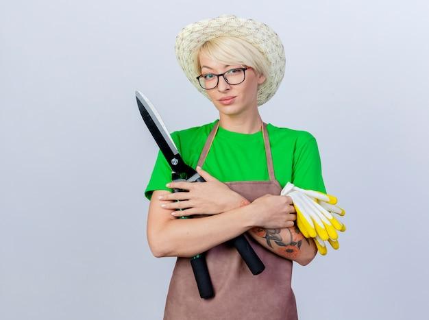 Młoda ogrodniczka z krótkimi włosami w fartuchu i kapeluszu, trzymająca nożyce do żywopłotu i gumowe rękawiczki, uśmiechnięta pewnie