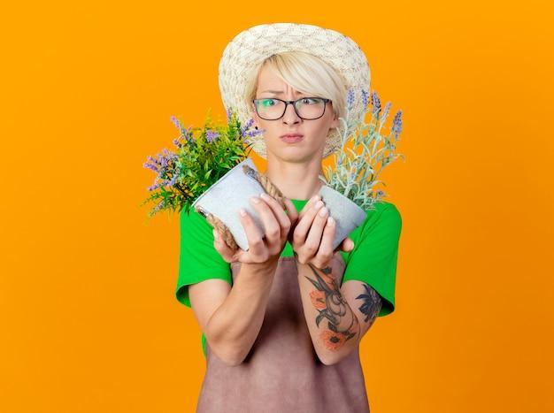 Młoda ogrodniczka z krótkimi włosami w fartuchu i kapeluszu trzymająca rośliny doniczkowe, patrząc na nich zdezorientowanych i niezadowolonych stojąc na pomarańczowym tle