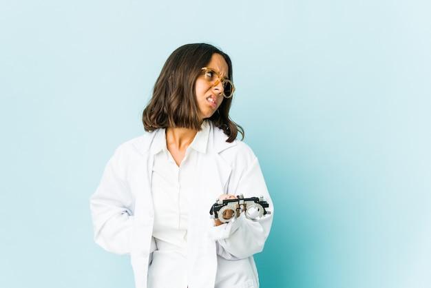 Młoda okulistka kobieta cierpi na ból pleców na izolowanej ścianie