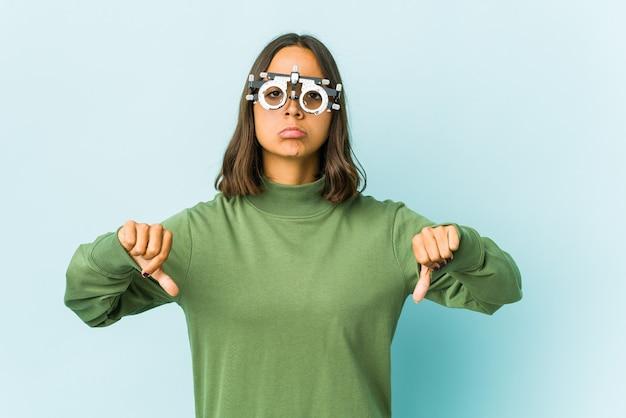 Młoda okulistka kobieta na odizolowanej ścianie pokazuje gest niechęci, kciuki w dół