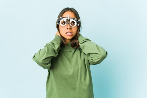 Młoda okulistka łacińska kobieta dotyka szyi, myśli i dokonuje wyboru.