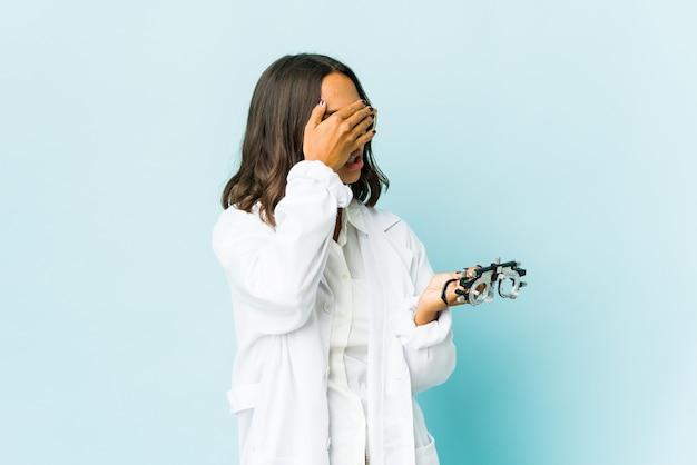 Młoda okulistka łacińska kobieta na izolowanej ścianie boi się zakrywających oczy rękami.