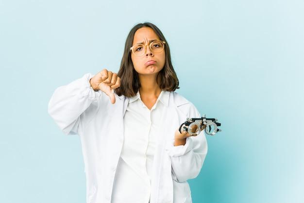 Młoda okulistka łacińska kobieta na odizolowanej ścianie pokazująca gest niechęci, kciuki w dół. pojęcie sporu.