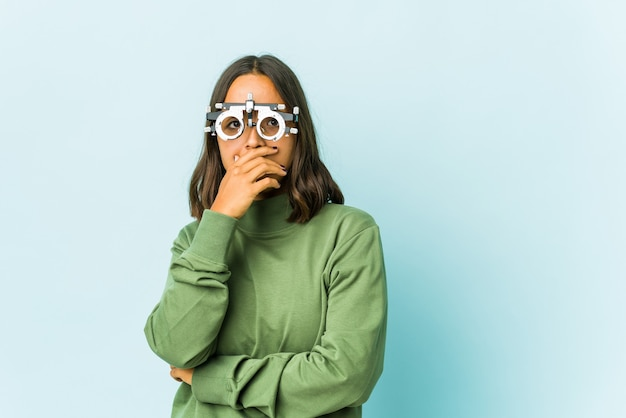 Młoda okulistka łacińska kobieta na odizolowanej ścianie przestraszona i przestraszona.