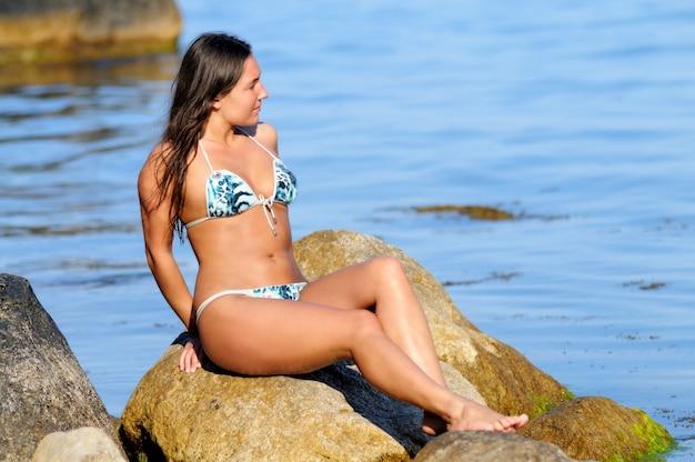 Młoda opalona dziewczyna w stroju kąpielowym, uśmiechnięta i pozowanie, leżąc na plecach na głazie nad brzegiem morza