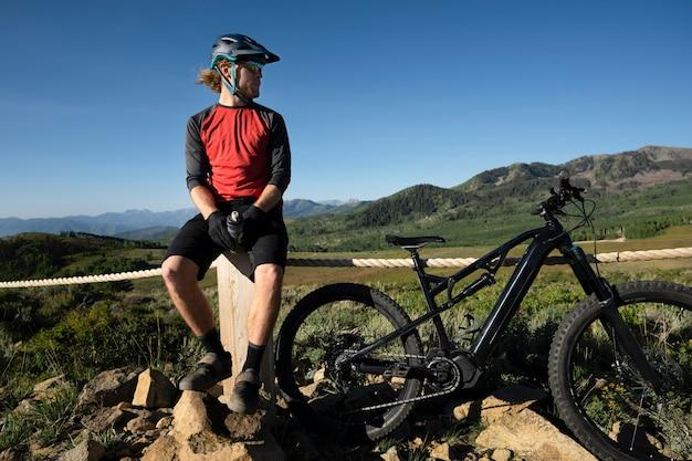Młoda osoba dorosła korzystająca z roweru elektrycznego na wsi