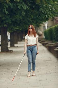 Młoda osoba niewidoma z długą laską spaceru po mieście