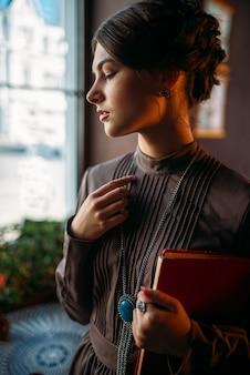 Młoda osoba płci żeńskiej stoi wewnątrz kawiarni