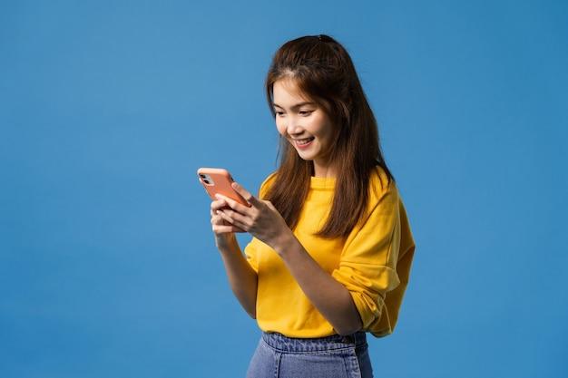 Młoda pani asia, korzystająca z telefonu z pozytywnym wyrazem twarzy, szeroko uśmiechnięta, ubrana w zwykły strój, czująca szczęście i stojąca odizolowana na niebieskim tle. szczęśliwa urocza szczęśliwa kobieta raduje się z sukcesu.