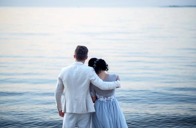 Młoda panna młoda i pan młody blisko morza na plaży o zachodzie słońca