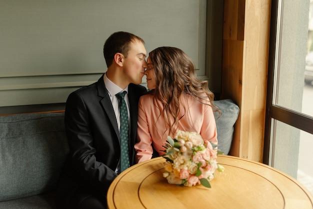 Młoda panna młoda i pan młody w kawiarni. mąż i żona trzymają się za ręce.