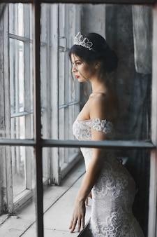 Młoda panna młoda w koronkowej sukni z nagimi ramionami i diademem na głowie, patrząc przez okno