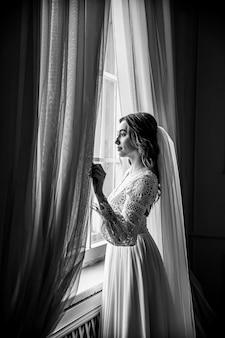 Młoda panna młoda w pięknej koronkowej sukience boho stoi przy oknie.