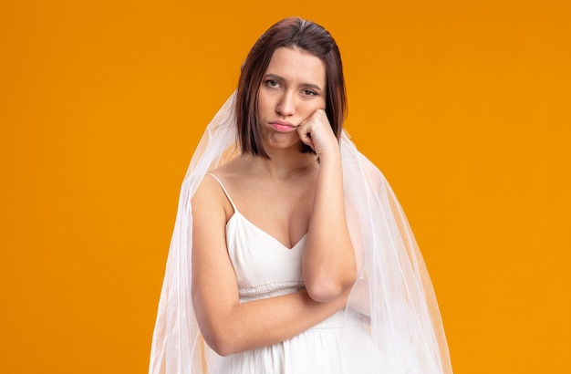 Młoda panna młoda w pięknej sukni ślubnej zmęczona i znudzona stojąc na pomarańczowo