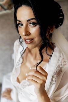 Młoda panna młoda w ślubnej sukni mienia bukiecie, studio strzał