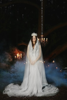 Młoda panna młoda z koroną i welonem na głowie stoi w lesie i pozuje na zewnątrz, bajkowy obrazek