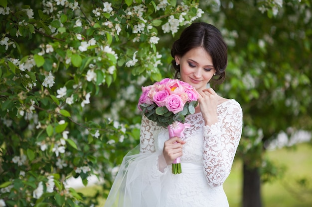 Młoda panna młoda z różowym bukietem ślubnym w kwitnącym ogrodzie