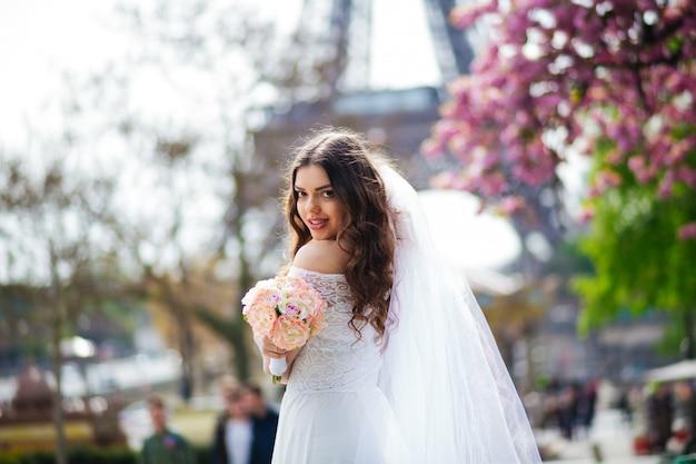 Młoda panny młodej pozycja przed wieżą eifla w paryż, francja