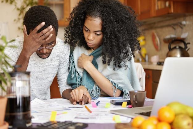 Młoda para afroamerykanów z wieloma długami obliczająca rachunki za gaz i prąd