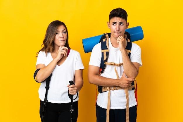 Młoda para alpinista z dużym plecakiem na żółto, mając wątpliwości i myślenie