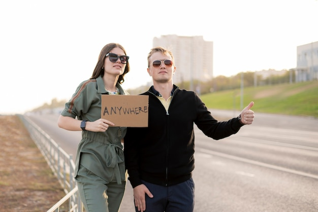 Młoda para autostopowiczów na autostradzie czeka na samochód, podróżuje z miłością w wolności