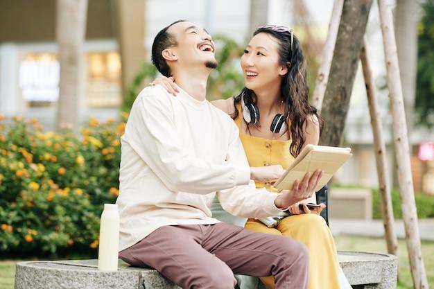 Młoda para azjatów siedzi na ławce i śmieje się podczas oglądania śmiesznych filmów na tablecie