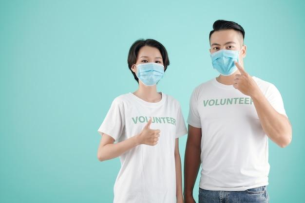 Młoda para azjatów wskazujących na maski ochronne i pokazująca kciuk w górę podczas wspólnego wolontariatu