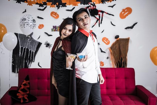 Młoda para azjatycka w kostiumach czarownicy i draculi z okazji halloween party i picie wina razem podczas festiwalu halloween w pokoju w domu. koncepcja para świętować halloween razem w domu.