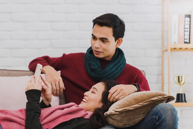 Młoda para azjatyckich kochanek zakupy online za pomocą karty kredytowej i smartfona w urządzonym pokoju
