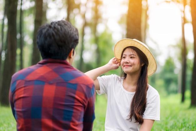 Młoda para azjatyckich kochanków siedzi razem w parku
