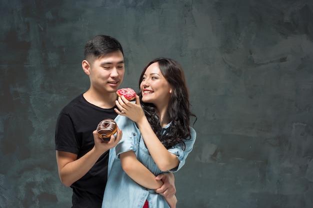 Młoda para azjatyckich lubi jeść słodkie kolorowe pączki