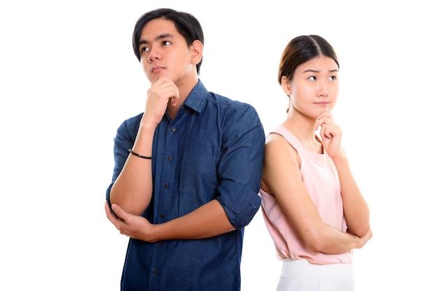 Młoda para azjatyckich myślenia razem na białym tle
