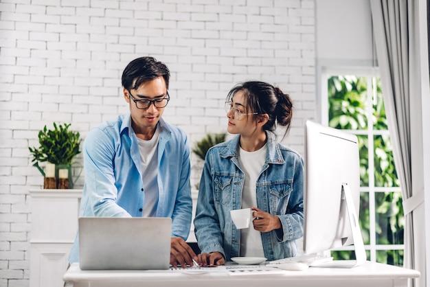 Młoda para azjatyckich relaks przy użyciu komputera stacjonarnego w pracy