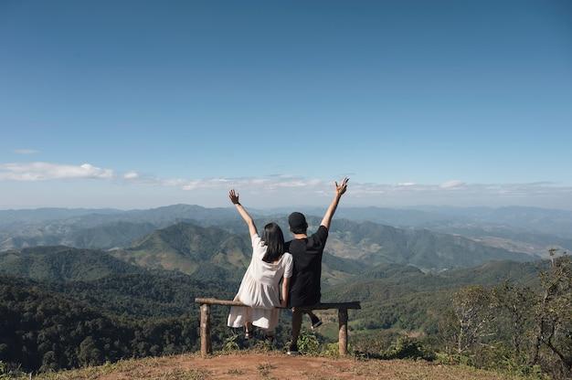 Młoda Para Azjatyckich Siedzi Podniósł Ręce Na Szczycie Wzgórza Premium Zdjęcia