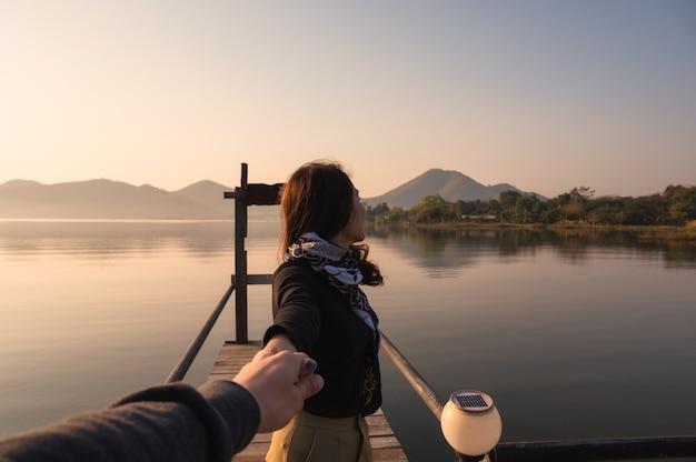 Młoda para azjatyckich, trzymając się za ręce na drewnianym molo z wschodem słońca