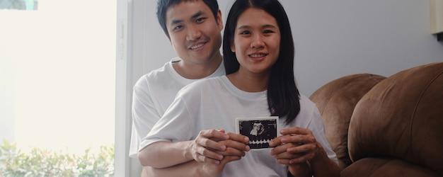 Młoda para azjatyckich w ciąży pokazać i patrząc zdjęcie usg dziecka w brzuchu. mama i tata czują się szczęśliwi, uśmiechając się spokojnie, podczas gdy dbają o dziecko leżące na kanapie w salonie w domu.