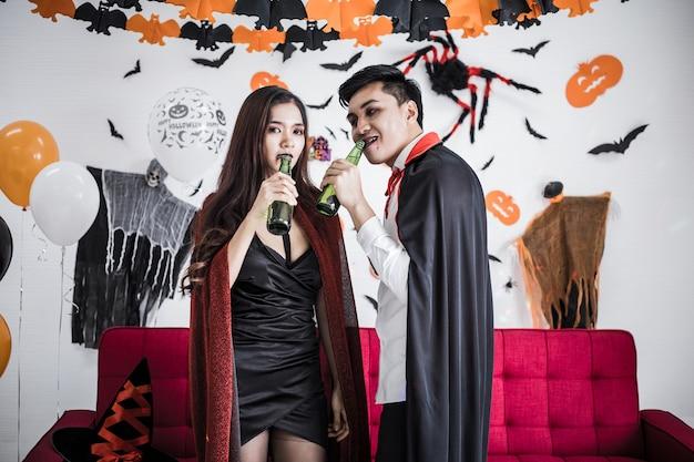 Młoda para azjatyckich w kostiumach czarownicy i draculi z okazji halloween party i picie piwa razem w halloween festival w pokoju w domu. koncepcja para świętować halloween razem w domu.